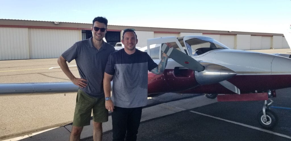 Two Caucasian men smiling next to a propeller
