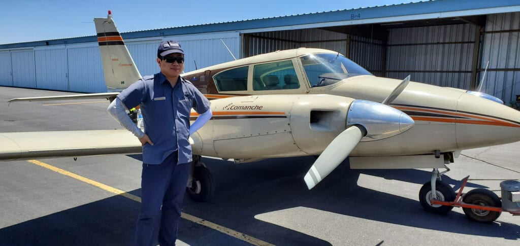 Man wearing a cap and sunglasses next to an aircraft.