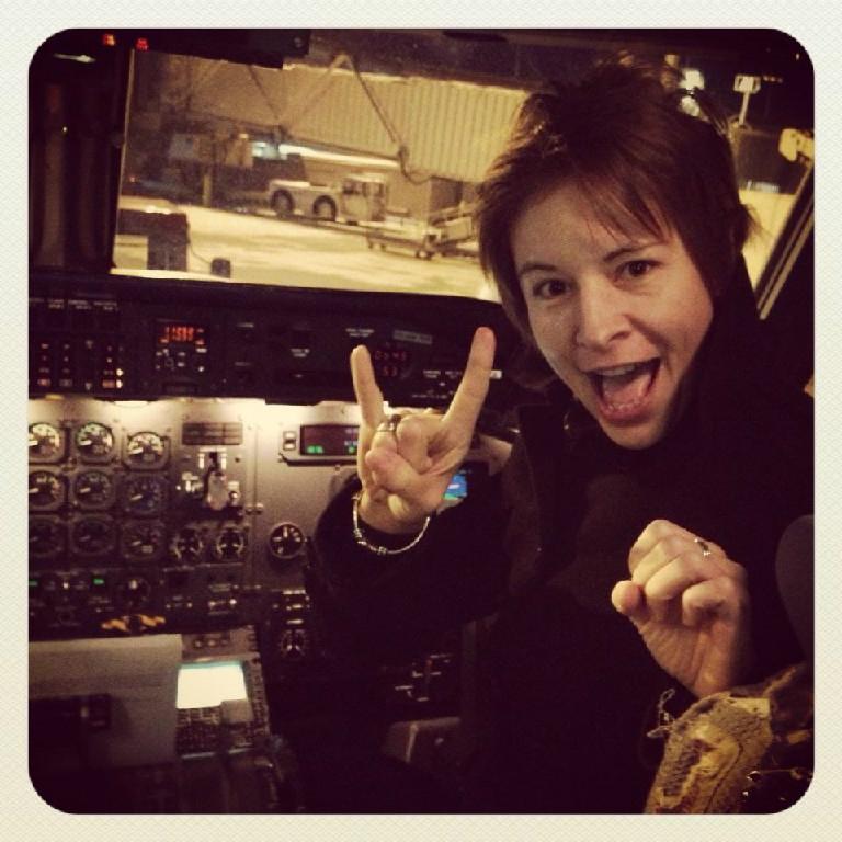 A pilot posing inside the cockpit.