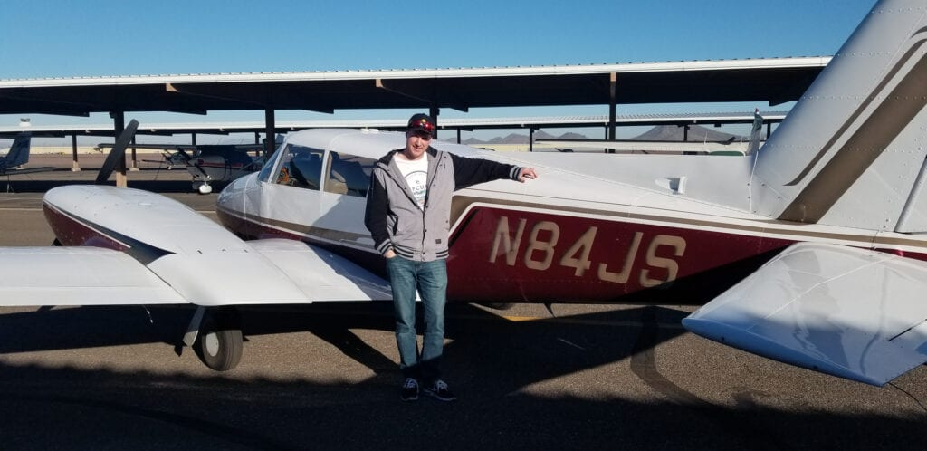 A man in a gray jacket and cap beside a small aircraft.