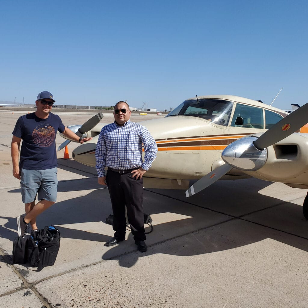 Two men in sunglasses posing in front of an aircraft.