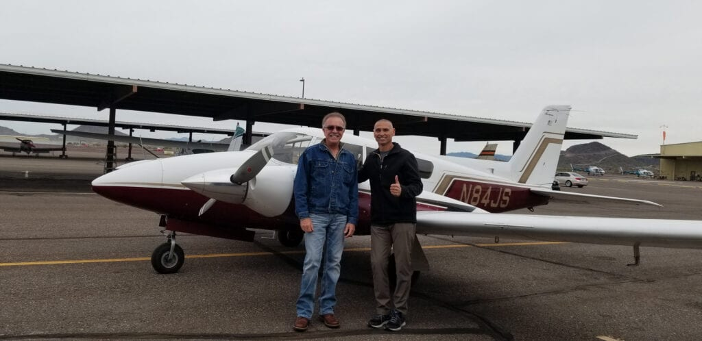 Men in jackets posing and smiling in front of an airplane.