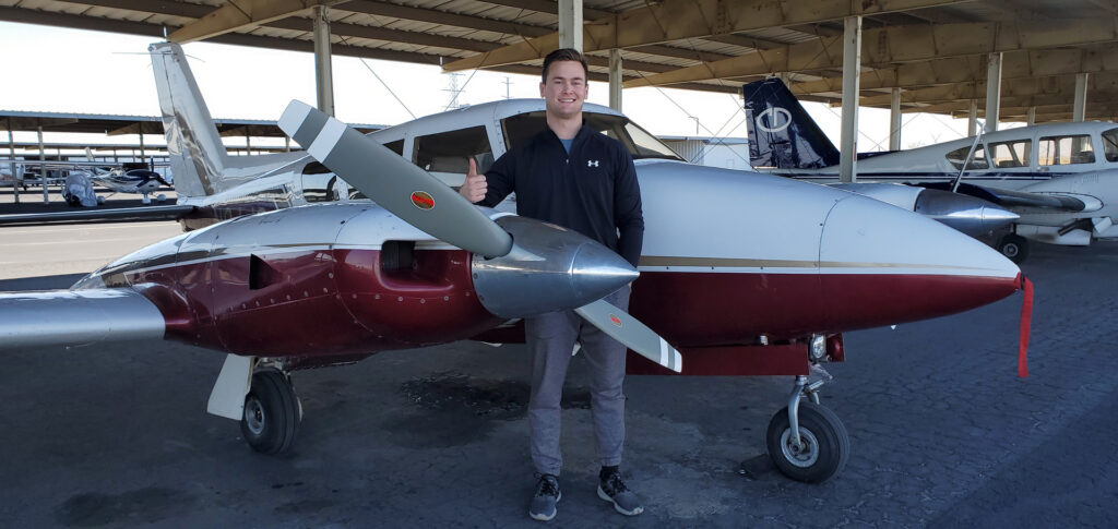 Man in a thumbs up pose next to a plane.