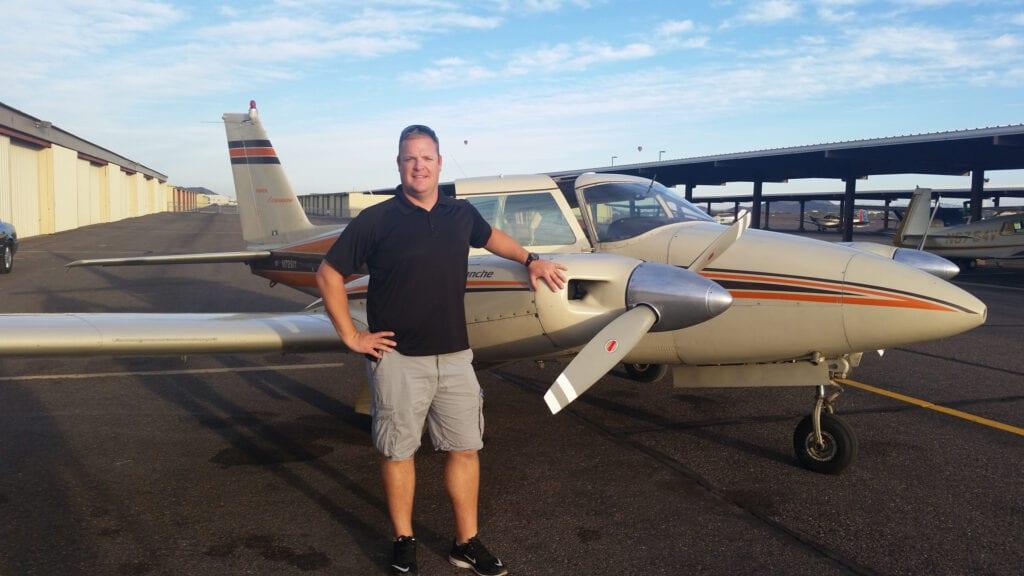 Caucasian man in a black shirt next to a plane propeller.