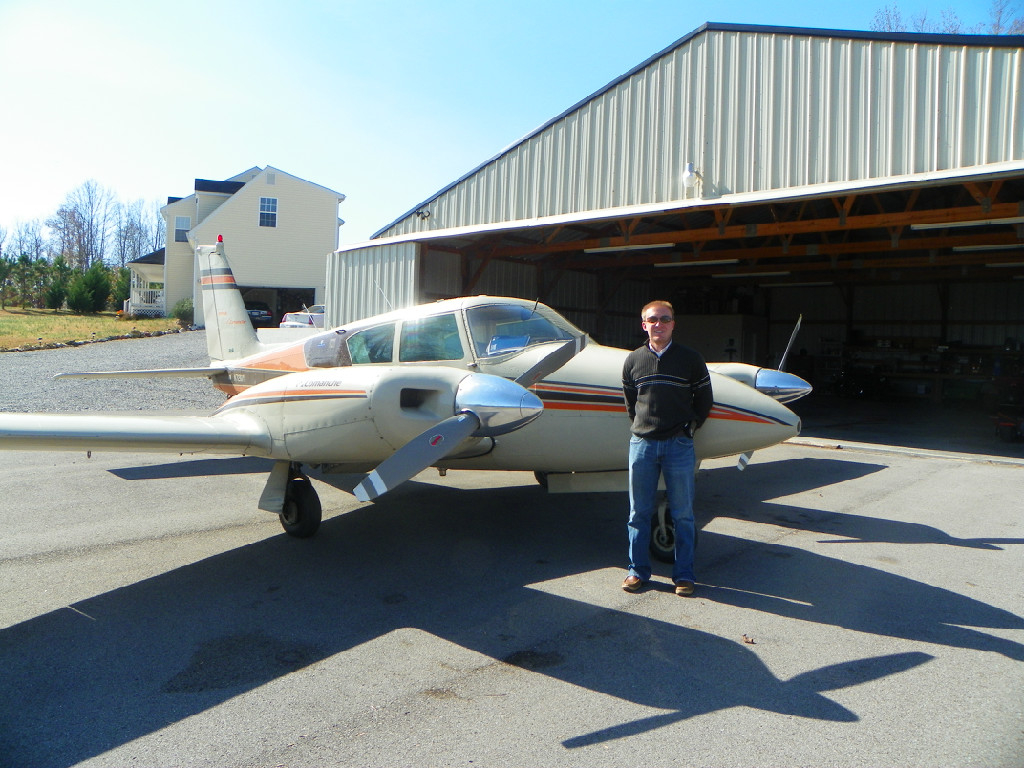 A man leaning against a small aircraft.