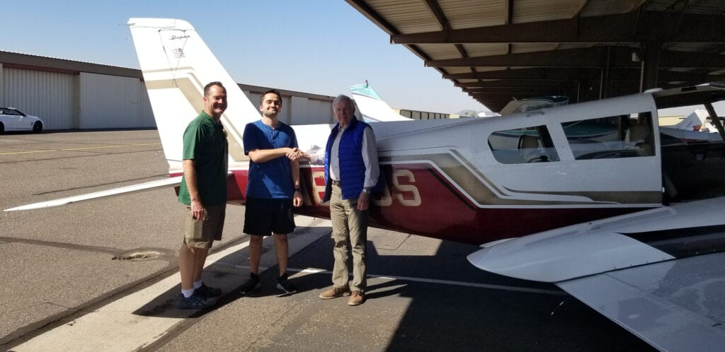 Three men posing beside a plane.