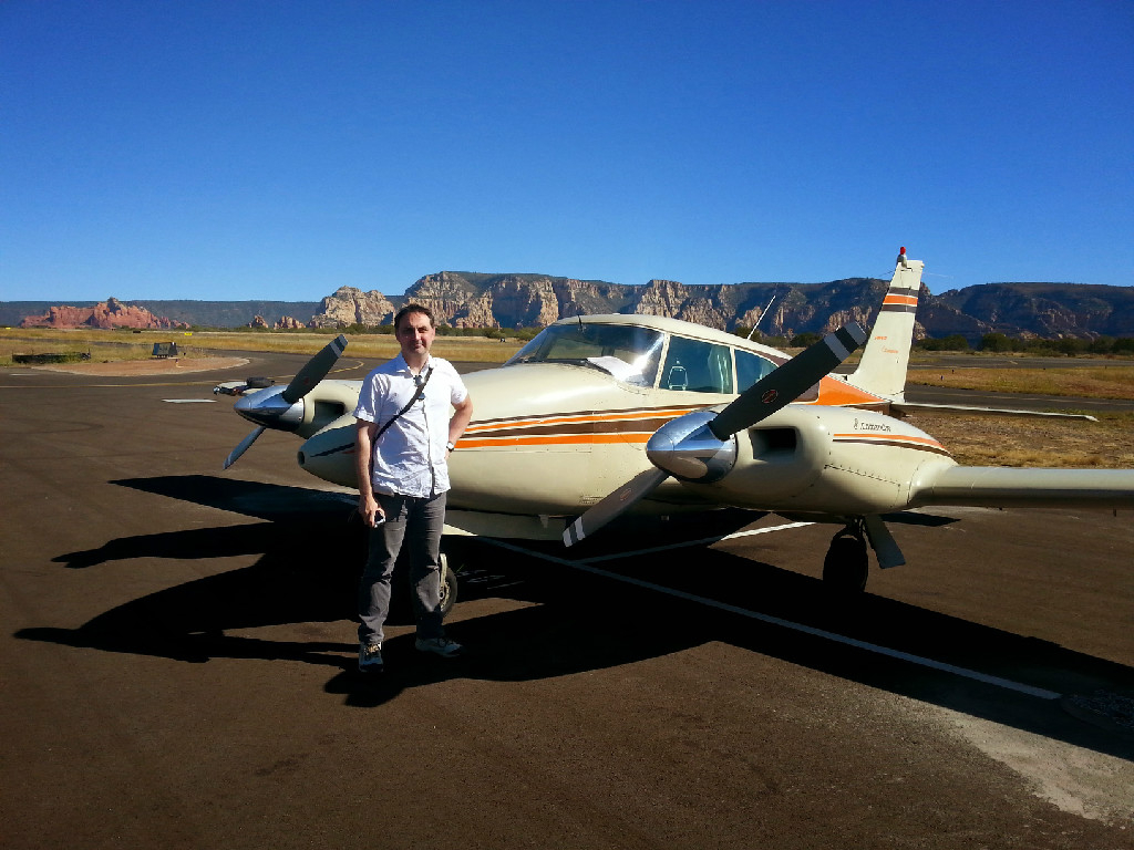A Caucasian guy in a white shirt posing in front of a plane.