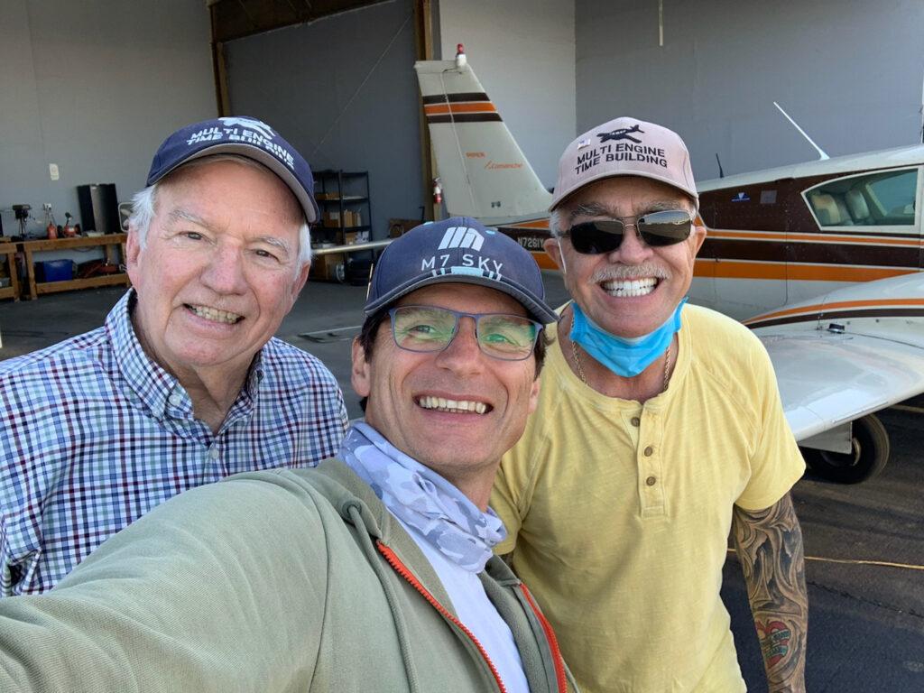 Three men smiling.