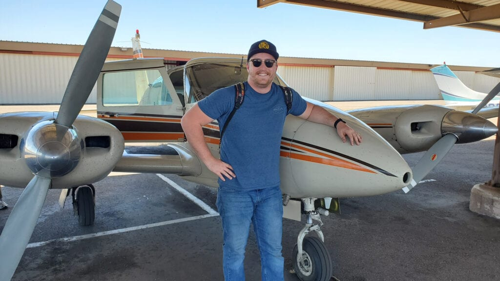 Man in a blue shirt and denim jeans smiling in front of an airplane.