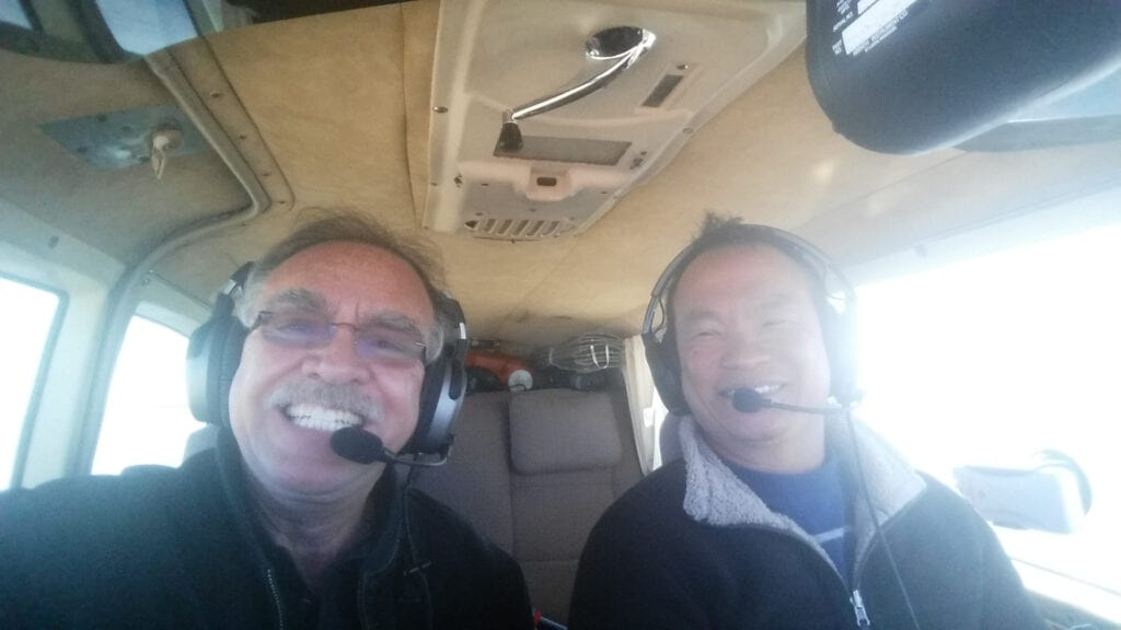 A Caucasian man and Asian man flying a plane.