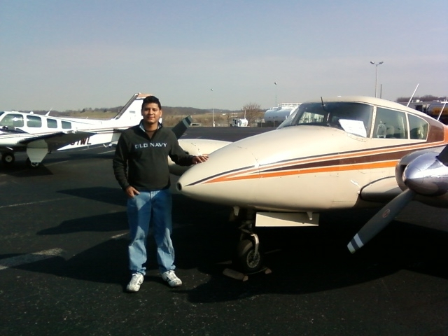 A guy in a black Old Navy sweater standing by an aircraft.