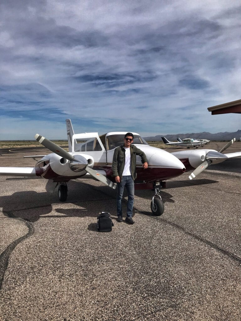 Man in a jacket posing in front on a small aircraft.