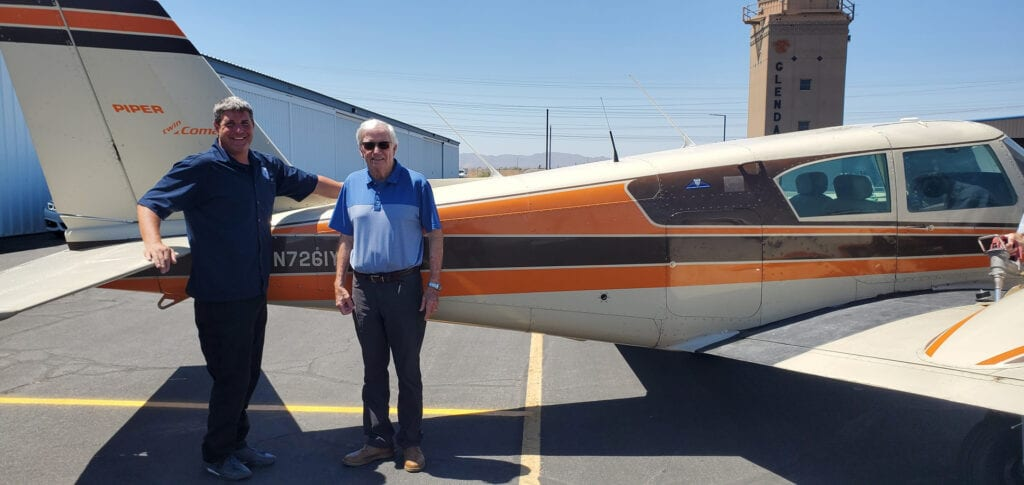 Two old men posing next to an aircraft.