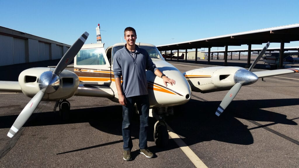 A Caucasian man standing and smiling next to a plane.