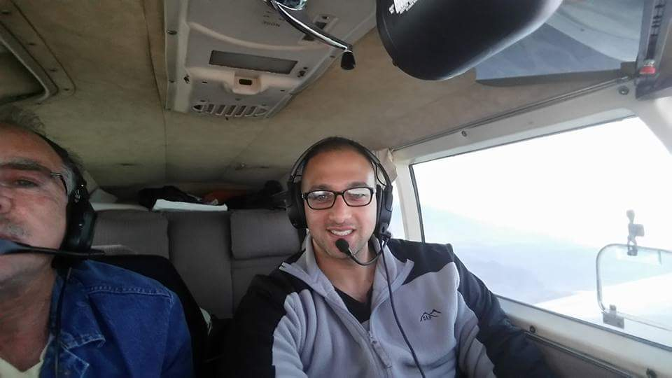 Two men in jackets flying an aircraft.