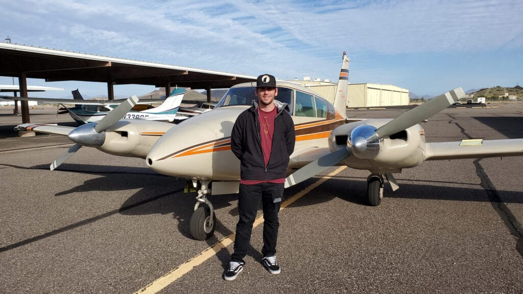 Person wearing a jacket and cap standing beside a plane.