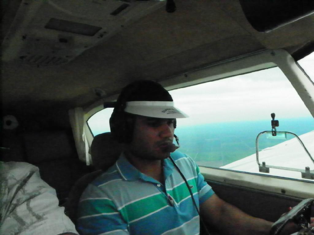 A man wearing a striped shirt driving the plane.