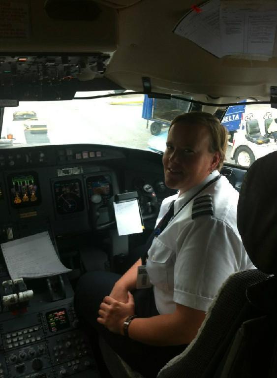 A female pilot sitting down.
