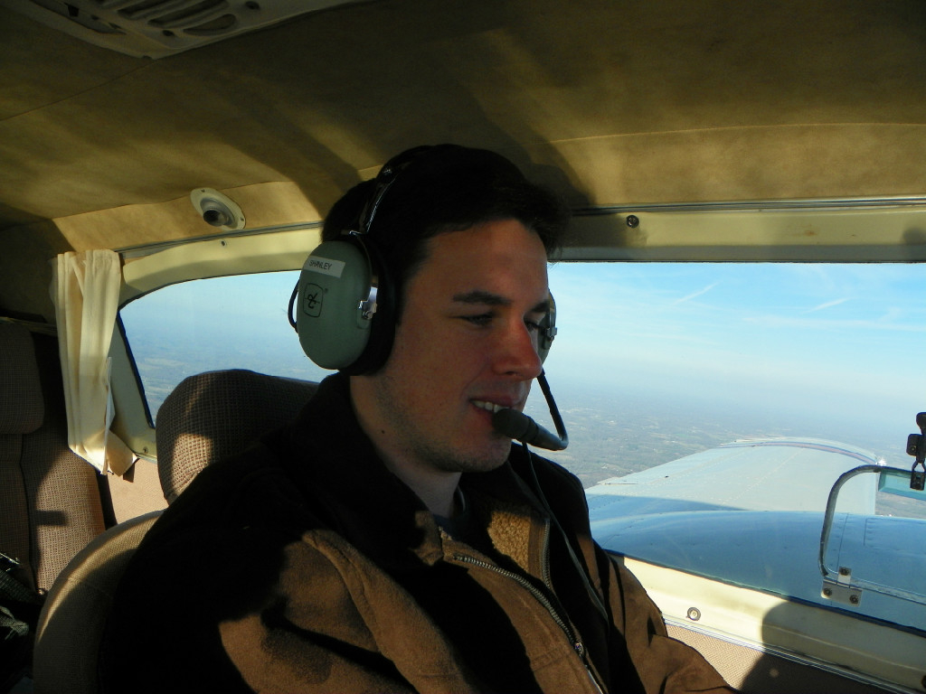 A Caucasian guy flying a plane.