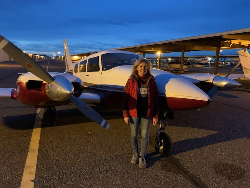 Old woman in a red jacket standing in front of an airplane.