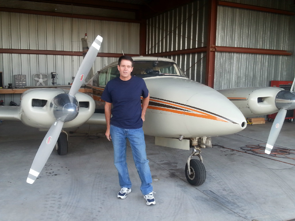 A guy standing in front of a plane inside the hangar.