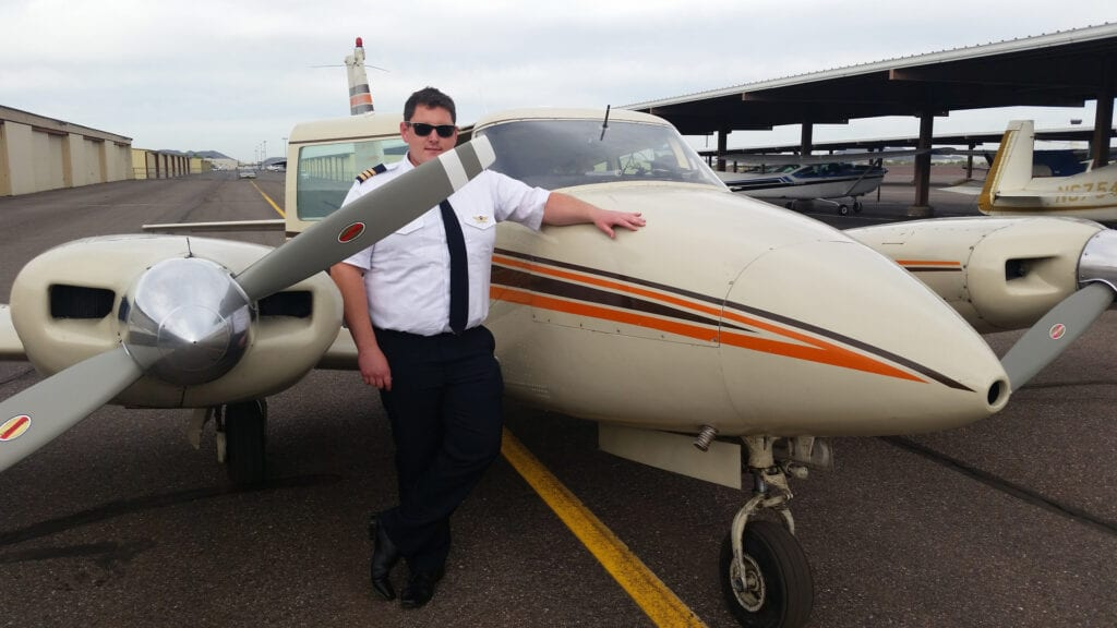Pilot posing next to a Piper Twin Comanche.