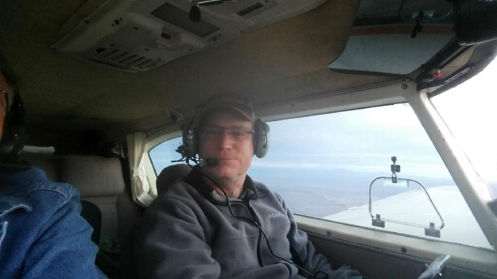 A pilot wearing a gray jacket.