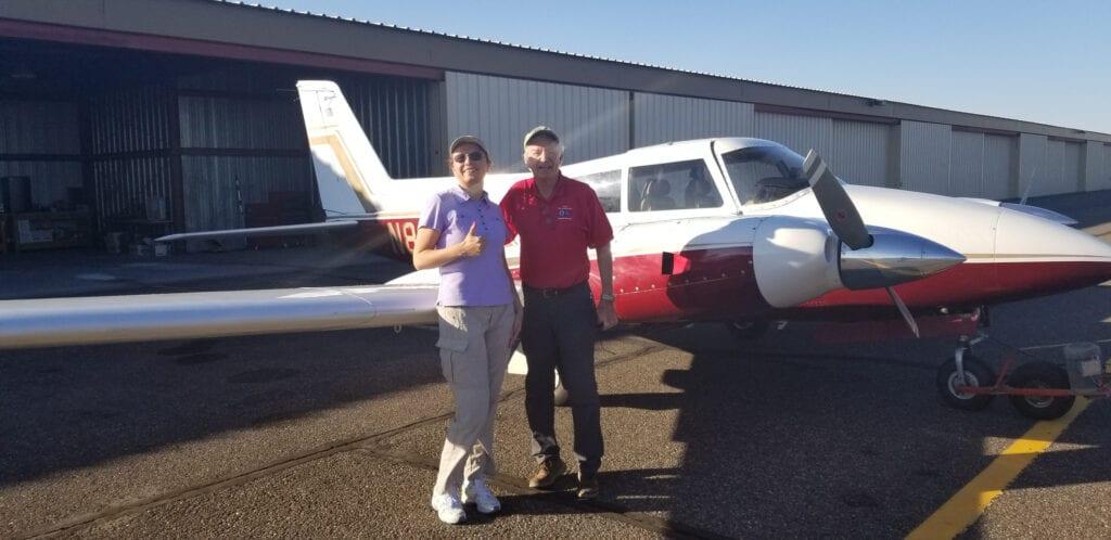 A man and woman standing beside an aircraft.