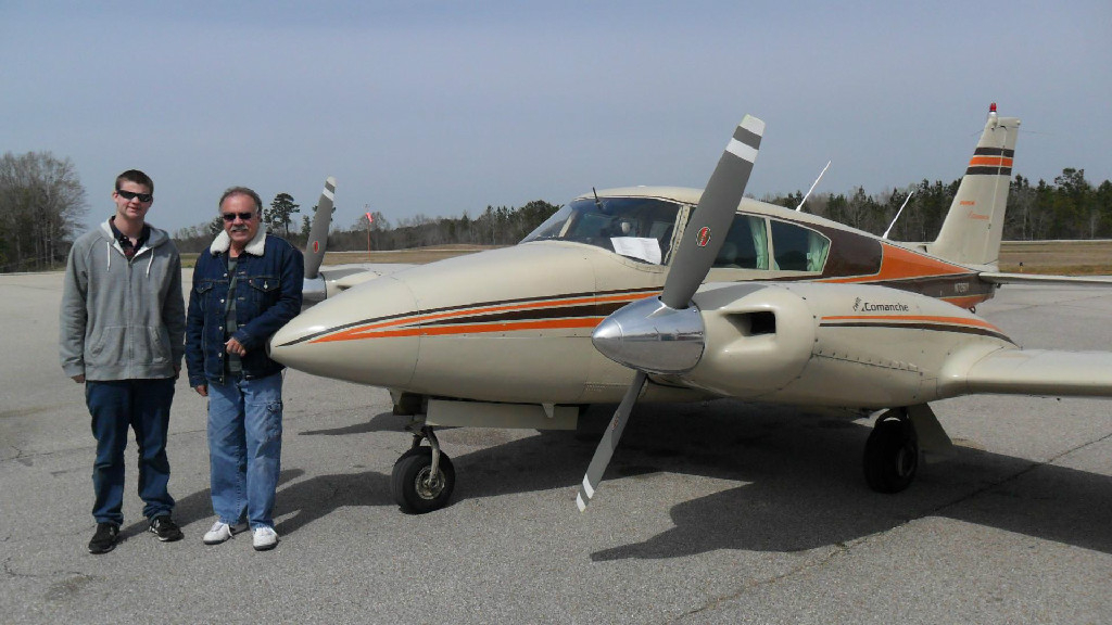 Two guys standing beside a small plane.