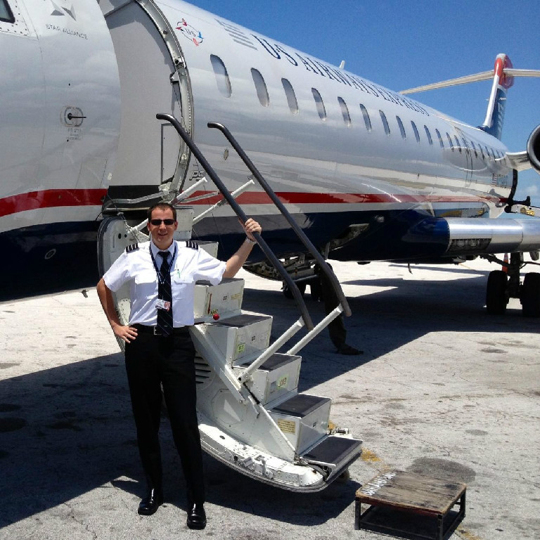 A pilot posing by the stairs to an airplane.