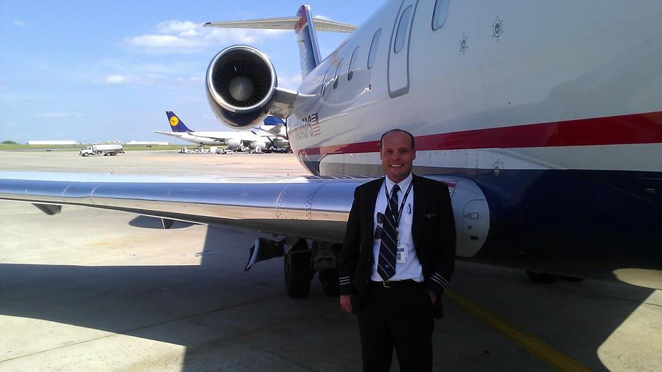 A pilot posing next to an airplane.