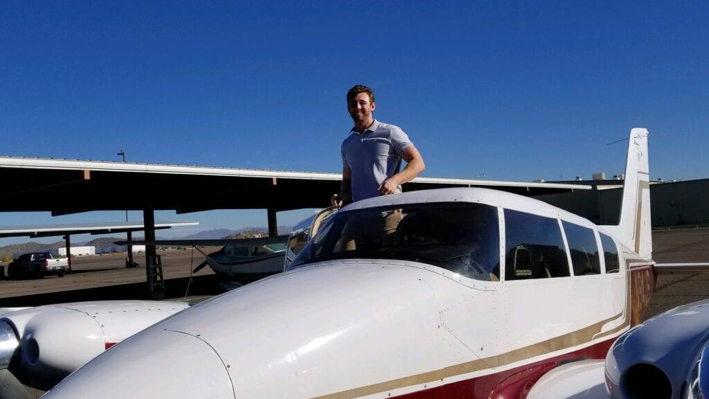 A man climbing inside a plane.