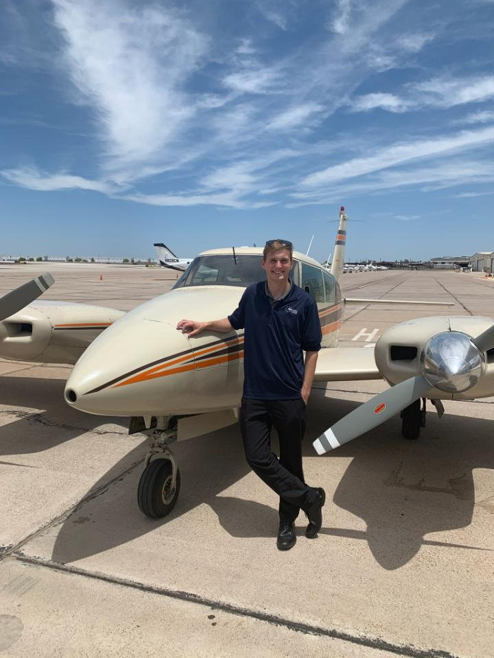 Man smiling in front of a Piper Twin Comanche.