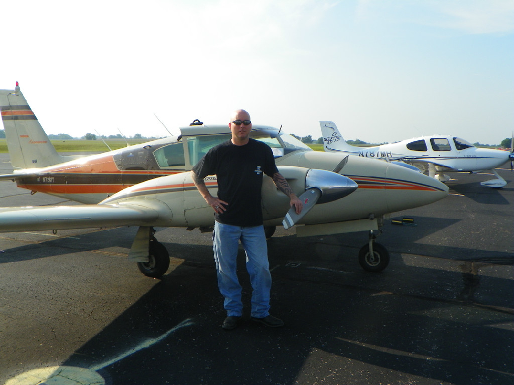 A bald man leaning against a propeller.