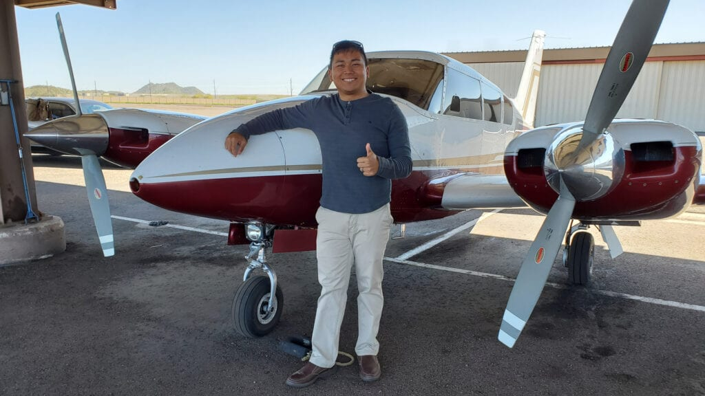 Man in a gray sweater smiling in front of an airplane.