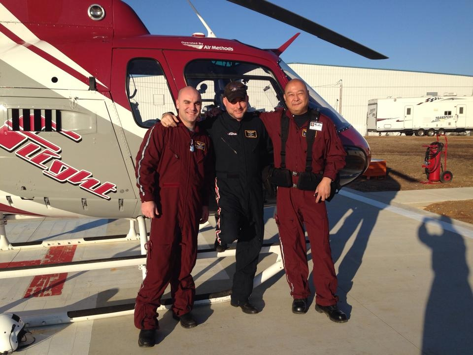 Three men in front of a helicopter.