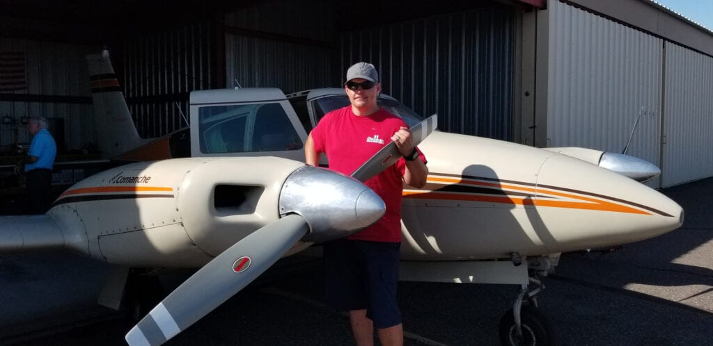 Man in a red shirt holding a propeller.