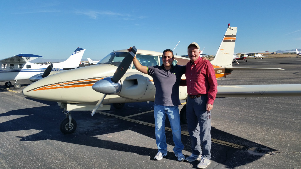 Two adult men posing in front of a small aircraft.