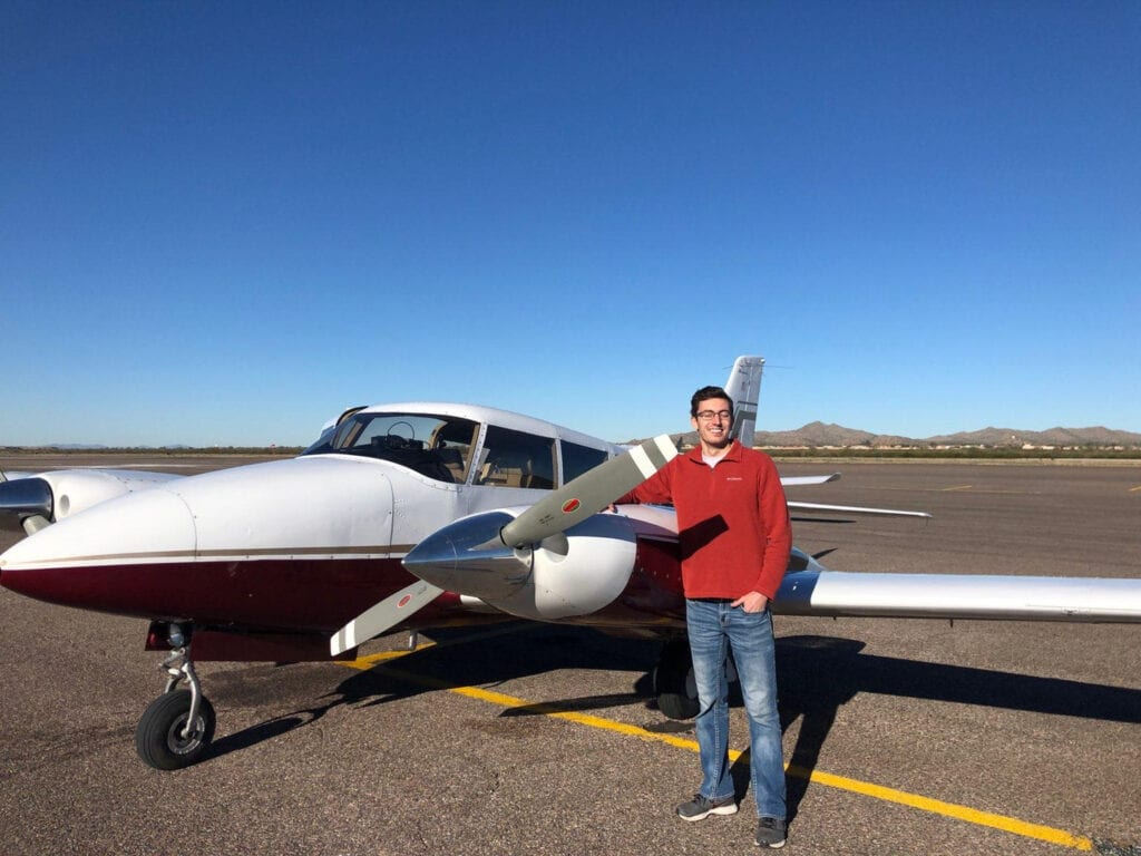 A man in a red jacket next to a small plane.