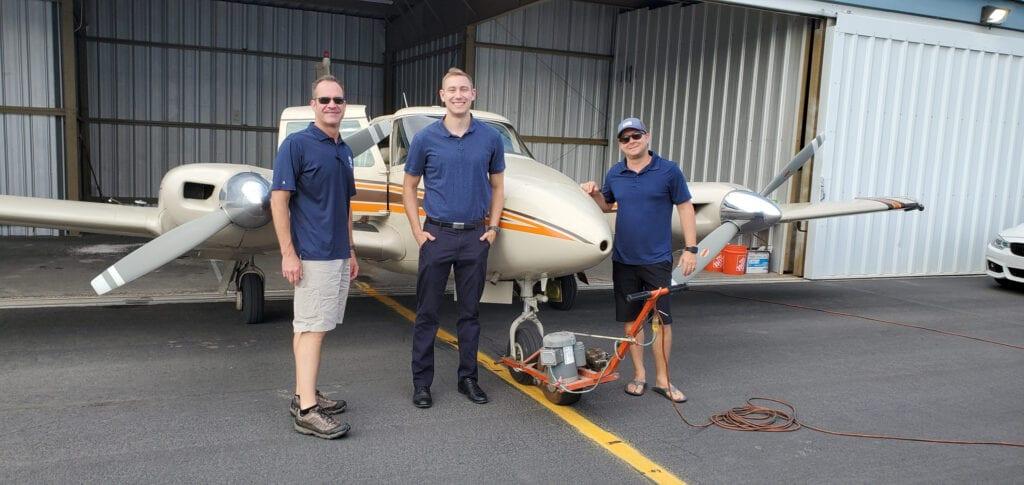 Three men in dark blue shirts in front of a plane.