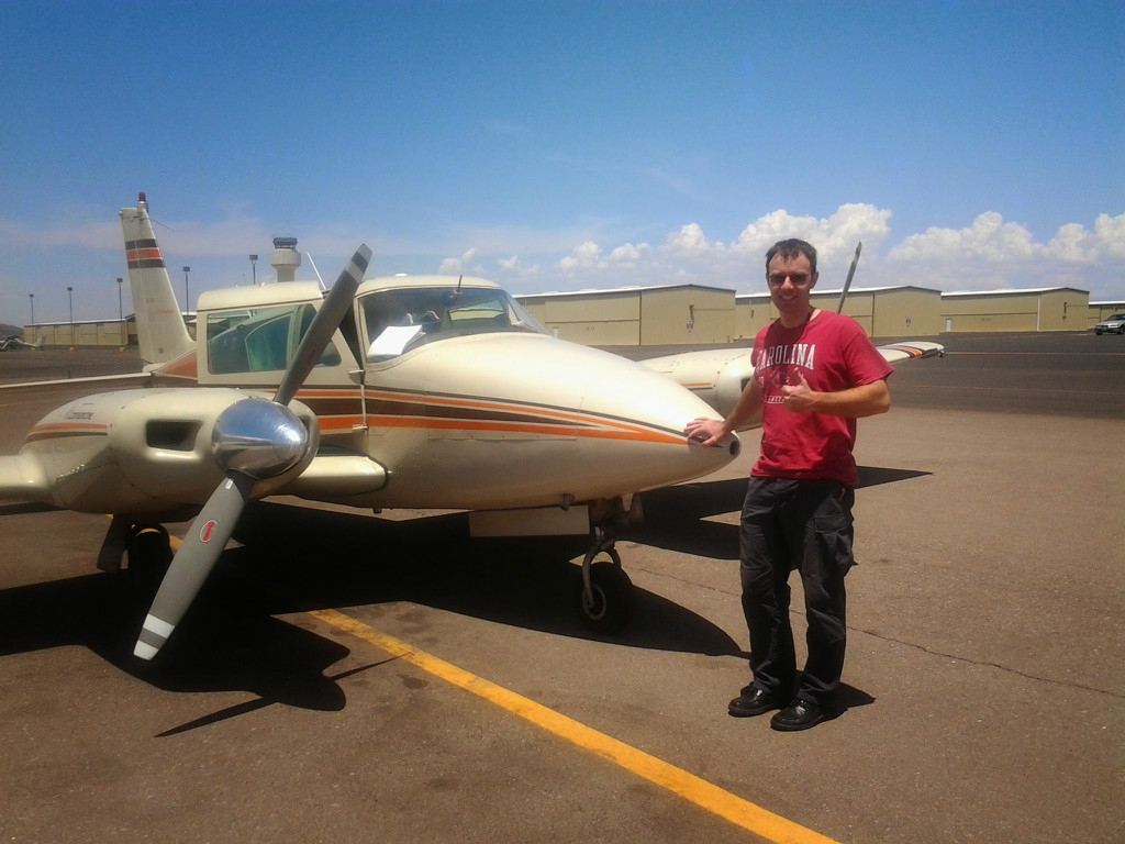 A person in a red shirt posing in front of an aircraft.