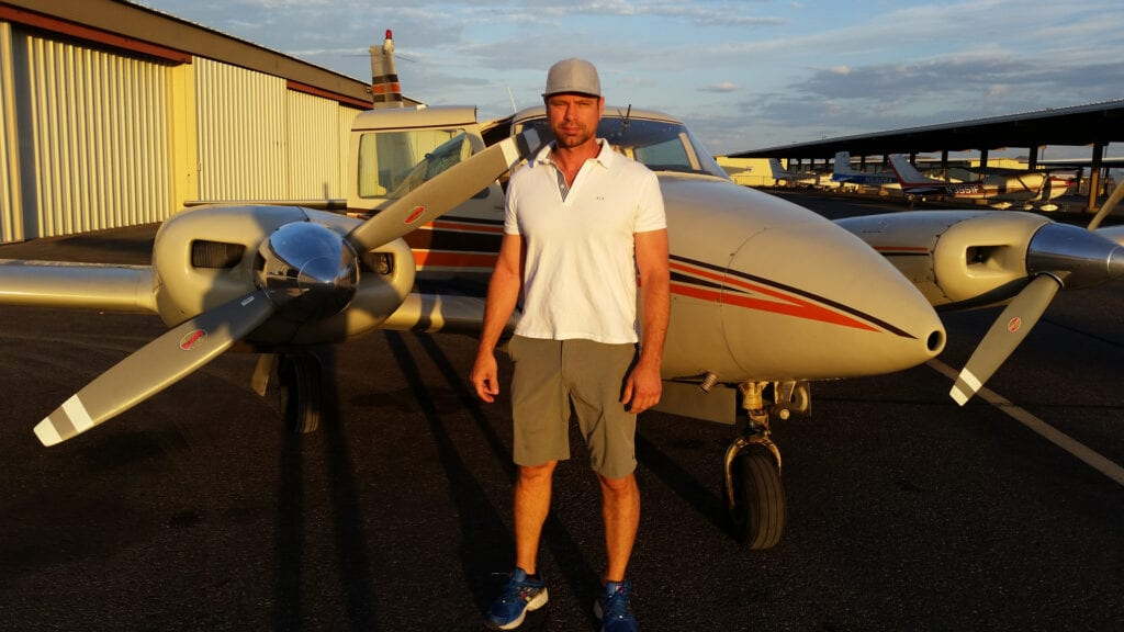 A Caucasian man wearing a white shirt and brown shorts.