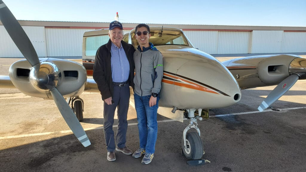 Two men in jackets smiling in front of a plane.