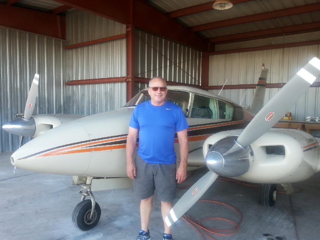 A man in a blue shirt standing next to a plane inside a hangar.