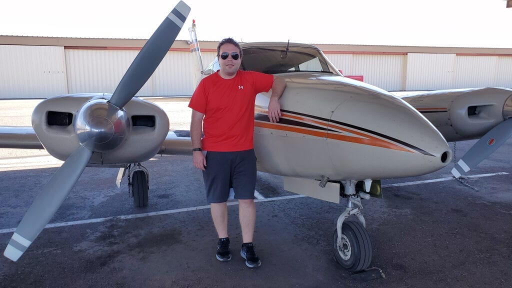 Man in a red shirt leaning against an aircraft.