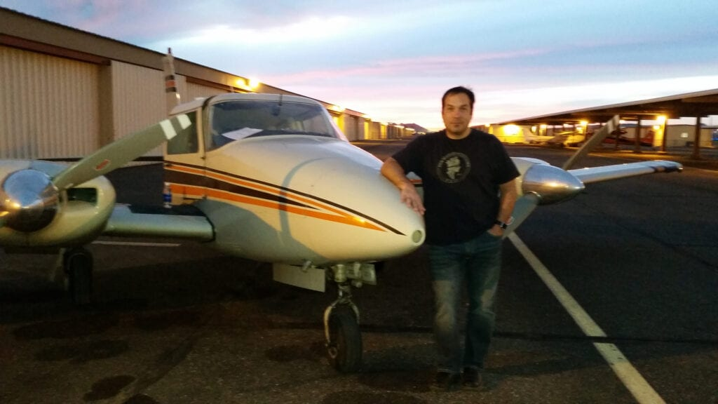 A Caucasian man posing next to a small aircraft.