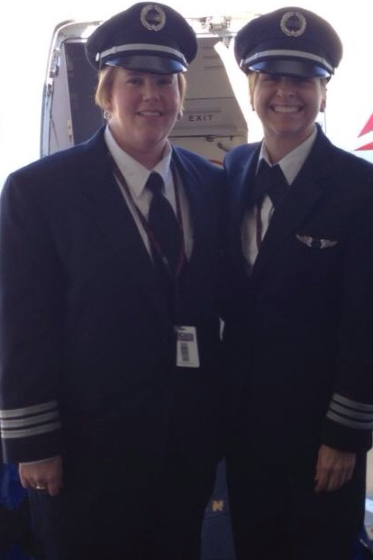 Two pilots standing beside each other smiling.