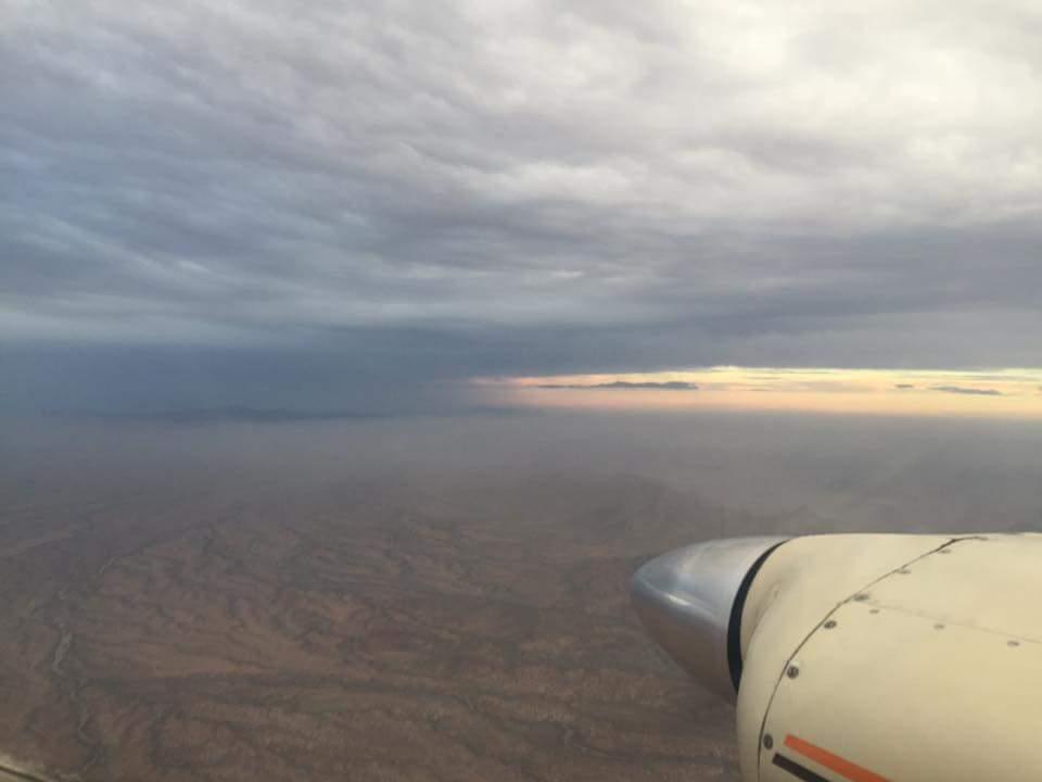 A plane flying underneath dark clouds.