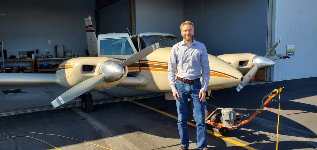Man standing in front of a Piper Twin Comanche.