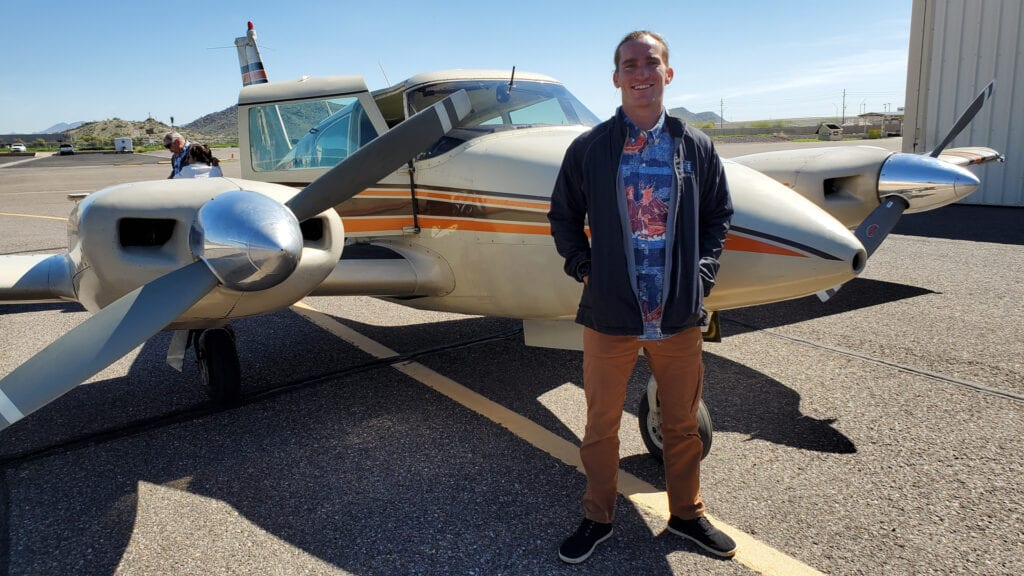 Man in khaki pants smiling in front of a plane.